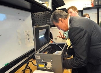Photo courtesy of Marshall University.  U.S. Sen. Joe Manchin positions a cell phone in a radio frequency isolation box in preparation for cell phone examination at Marshall University Forensic Science Center's Digital Forensics Investigative Unit.