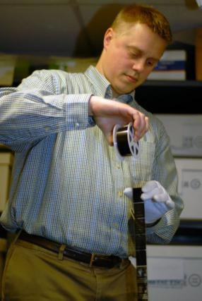 Kyle Campbell, with the West Virginia Division of Culture and History, displays a roll of microfilm.