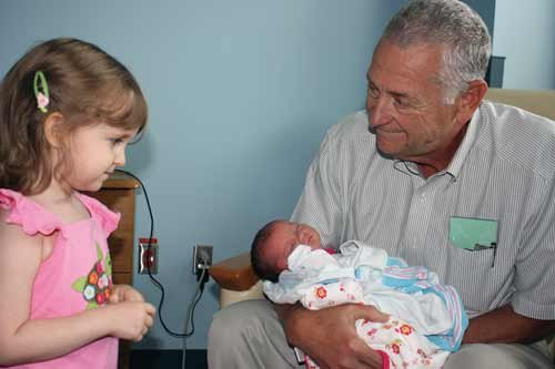 Pochick holds one of his eight grandchildren, Charlotte Hayes, on the day she was born as her sister, Olivia, looks on.