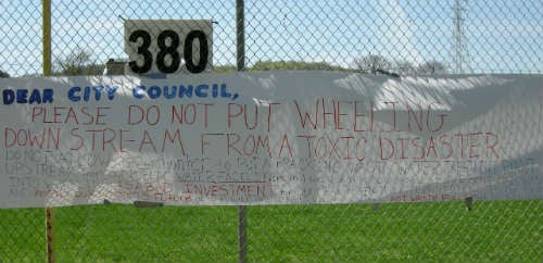 """""""Please do not put Wheeling downstream from a toxic disaster,"""" reads a sign at an April 21 rally opposing the facility."""