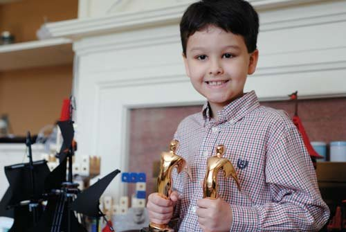 "Photo by Andrea Lannom. Justus Loughry poses with the two Telly Awards his family won. Justus won a Telly award for his role in ""The Real Justus Loughry,"" and the Loughry campaign won another Telly Award for all of its campaign commercials."