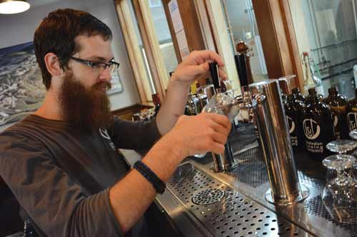 Charleston Brewing Company Bartender Joshua Jenkins pours a Westward Gaze Red Ale, one of eight craft beers on tap.