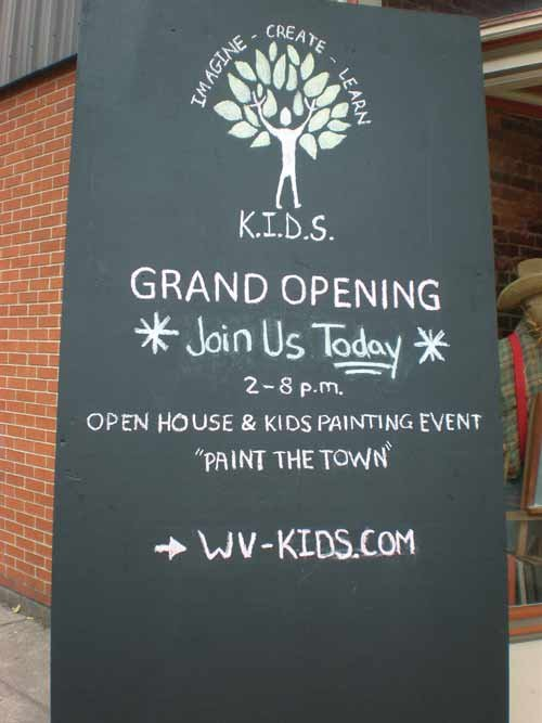 A sign announcing K.I.D.S. grand opening welcomes attendees inside.
