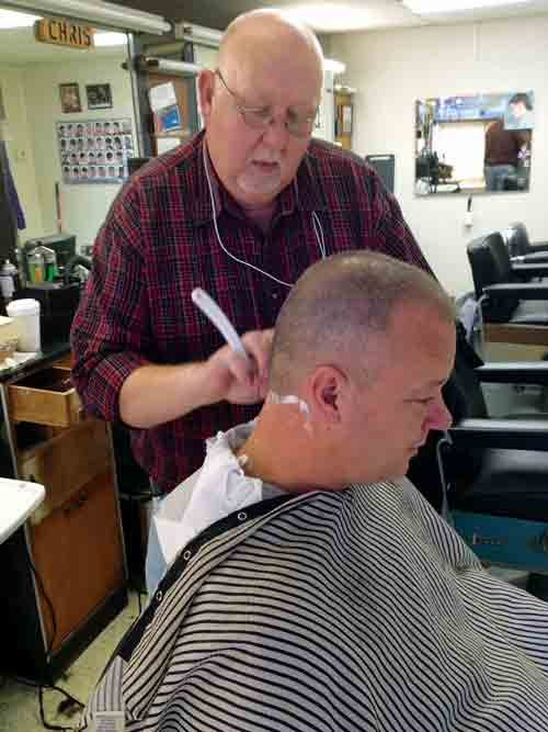 Paul Bryant of Drive-In Barber Shop in Kanawha City gives one of his regular customers, David Howell of Winifrede, a hot lather neck shave to complete his haircut.