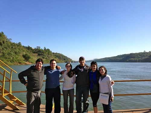 "Photo courtesy of Gerard D'Souza. ""Team ParagUSA"" on a barge crossing the river where Argentina, Brazil and Paraguay meet, known as the Triple Frontiers."