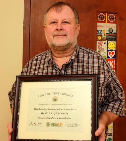 WLU professor David Thomas displays the REAP Award.