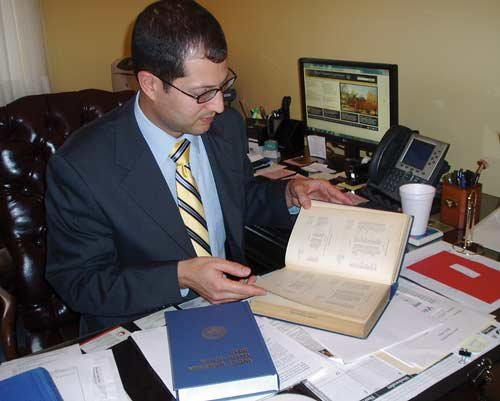 GEORGE HOHMANN / The State Journal. Assistant Clerk of the Senate Lee Cassis carefully handles a 1916 Blue Book — the first year the book was published.