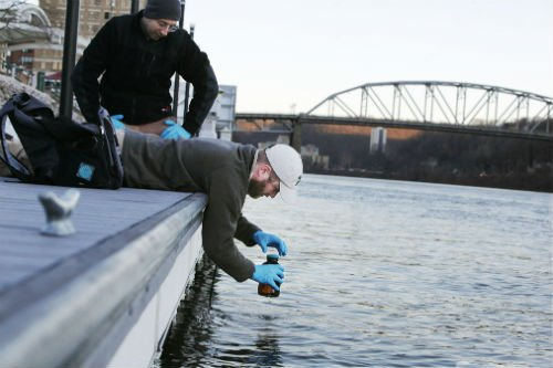 Jason Fillhart, from West Virginia Water Research Institute, leans off a boat dock to collect a water sample from the Elk River.