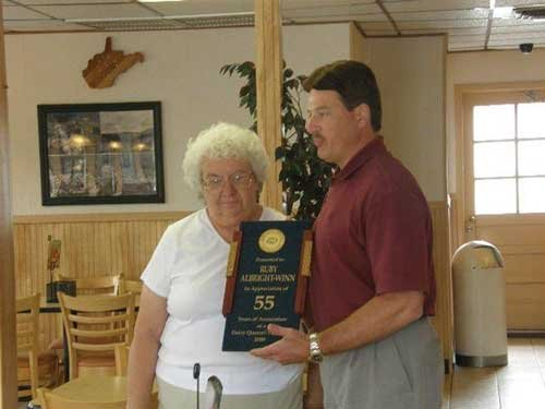 Photo courtesy Ruby Winn. DQ field consultant surprised Winn with the 55 year award, which she accepted in her Romney facility.