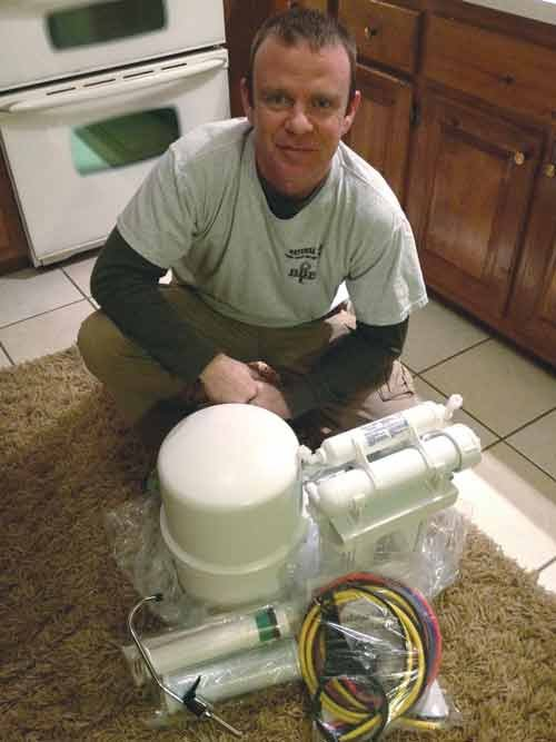 Photo courtesy of Chris Harry. Chris Harry with the reverse osmosis system.
