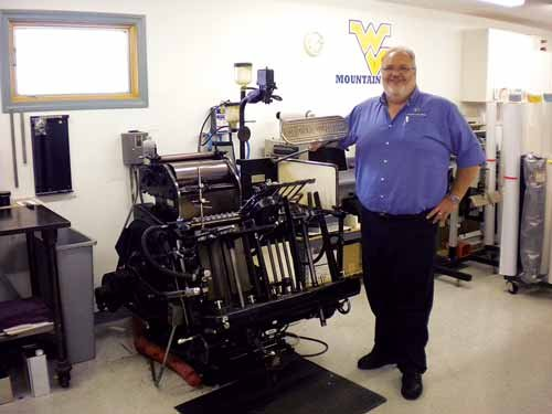Missy Sheehan / For The State Journal. Scott Schoppert, owner of Printing Impressions in Martinsburg, stands next to his original Heidelberg letterpress from 1955, which is still in use.