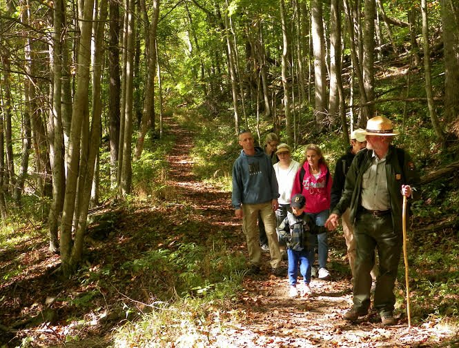 Hikers and a park ranger enjoy a walk along the Bluestone River. National Park Service photo.